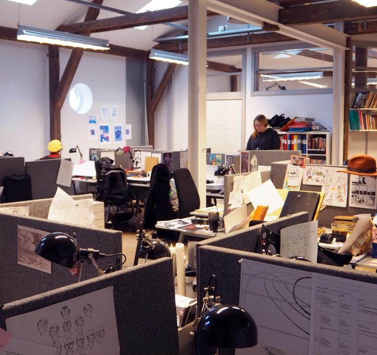 I stora ateljén arbetar deltagarna i kursen Serieskolan vid sina personliga bänkar.